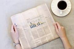 De jonge krant van de vrouwenlezing op grijze achtergrond stock afbeelding