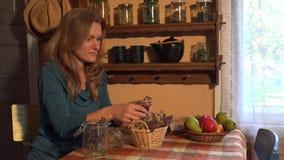 De jonge kruidkundigevrouw bereidt de kruiden van de oregomarjolein voor de wintertijd voor 4K stock video