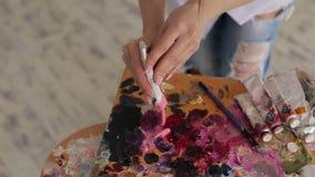 De jonge kunstenaar drukt de olieverf van de buis op het palet stock videobeelden