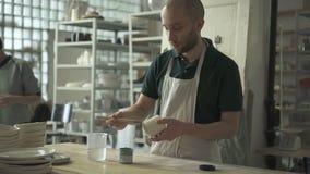 De jonge kunstenaar schildert op aardewerk in aardewerkstudio stock videobeelden