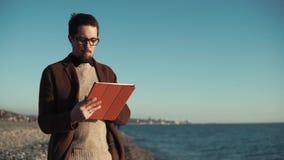 De jonge kunstenaar trekt een digitaal beeld op een draagbare tablet dichtbij het overzees stock videobeelden