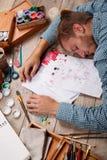 De jonge kunstenaar viel in slaap terwijl het trekken van zijn beelden stock foto's