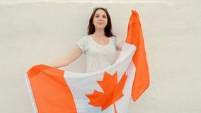 De jonge latino vrouw houdt de vlag van Canada voor haar lichaam die met trots en vreugde, wijnoogst lawaaierige korrelige lengte stock video