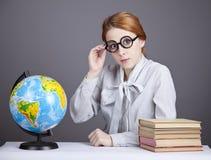 De jonge leraar in glazen met boeken en bol Royalty-vrije Stock Foto