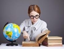 De jonge leraar in glazen met boeken en bol Stock Afbeelding