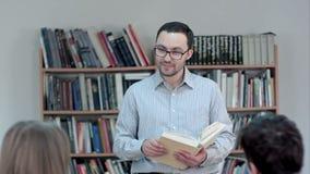 De jonge leraar met boek dient binnen schoolklaslokaal in die aan klasse spreken stock footage