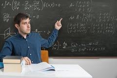 De jonge leraar richt op wiskundeformules op bord met vinger stock foto's