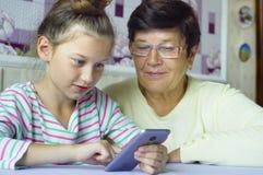 De jonge leuke grootmoeder van het kleindochteronderwijs hoe te om smartphone thuis te gebruiken stock foto