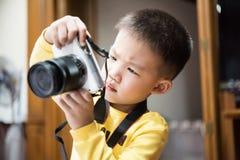 De jonge leuke jongen die en een foto houden schieten door witte camera Stock Afbeelding