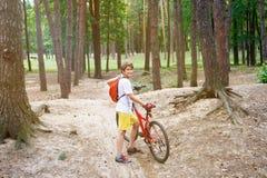 De jonge leuke jongen in helm berijdt een fiets in het park De jongen gaat op de weg Sport stock foto's
