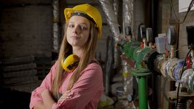 De jonge leuke meisjesbouwer bevindt zich dichtbij pijpen, glimlachend, kruisend wapens, lettend op bij camera, bouwend conceptie stock videobeelden