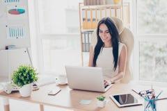 De jonge leuke onderneemster typt op haar laptop bij moderne offic royalty-vrije stock foto's