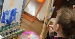 De jonge leuke vrouwelijke kunstenaar is in een kunststudio die, die achter een schildersezel zitten en op canvas schilderen Teke stock videobeelden