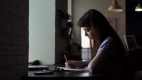 De jonge leuke vrouwelijke kunstenaar zit bij de lijst en trekt in een notitieboekje stock footage