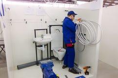 De jonge loodgieter installeert materiaal voor badkamers stock afbeelding
