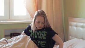 De jonge luie blondevrouw gaat bed in vroege ochtend weg stock videobeelden