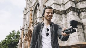 De jonge maar ervaren reiziger maakt selfie dichtbij de kerk in de stad De kerel glimlacht en kijkt gelukkig royalty-vrije stock afbeeldingen