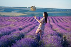 De jonge magische aanbiddelijke vrouw op lavendelgebied die op de zomerdag en geniet het levens van tijd met de macht van het vro stock afbeelding