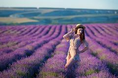 De jonge magische aanbiddelijke vrouw op lavendelgebied die op de zomerdag en geniet het levens van tijd met de macht van het vro stock afbeeldingen