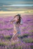 De jonge magische aanbiddelijke vrouw op lavendelgebied die op de zomerdag en geniet het levens van tijd met de macht van het vro stock foto