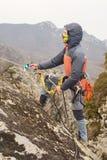 De Jonge Man beklimt de rots op een kabel met veiligheidsgordels, verzekering en kabel, in volledige alpinismemateriaal en a Stock Afbeelding
