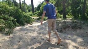 De jonge man die door het zand blootvoets ploeteren Limps, wankelt, zet zijn voet op tiptoe Hersenverlamming in volwassenheid stock videobeelden