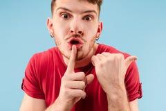 De jonge man die een geheim achter haar fluisteren overhandigt blauwe achtergrond royalty-vrije stock afbeelding