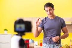 De jonge man die over voedselsupplementen blogging stock foto's