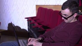 De jonge man die in zonnebril bij concertzaal op zijn laptop typen stock videobeelden