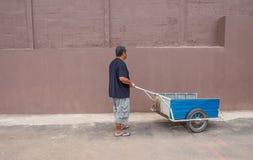 De jonge man duwt een oude kar Stock Foto