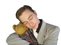 De jonge man in een kostuum, dat een stuk speelgoed omhelst draagt Stock Foto