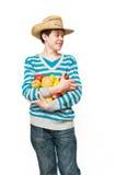De jonge man in een strohoed met fruit Stock Foto