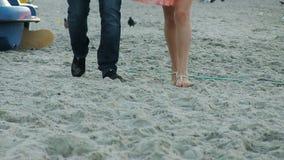 De jonge man en een vrouw lopen langs de kust minnaars Tegen de achtergrond van de zonsopgang stock video