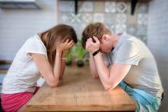 De jonge man en de vrouw hebben een ruzie in keuken thuis, het conflict van het paarhuishouden, zorg en het verdriet, kan ` t opl stock foto