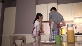 De jonge man en de vrouw werken samen Zij wast glazen Hij droogt hen met keukenhanddoek op De kerel glimlacht Hij stock video