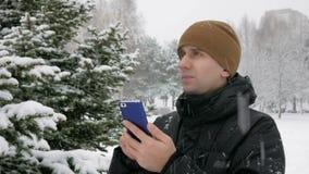 De jonge man gaat in een de winterbos in de sneeuw en is georiënteerd over de telefoon Hij zoekt de juiste richting stock videobeelden
