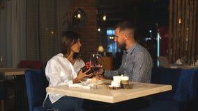 De jonge man geeft een gift aan een jong meisje in de koffie stock videobeelden