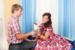 De jonge man geeft een mooie vrouwenbloemen stock afbeeldingen