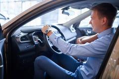 De jonge man kiest een nieuwe auto Het concept het kopen van een nieuwe auto stock foto