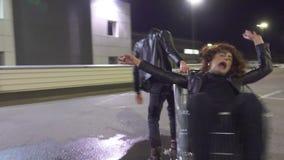 De jonge man in leerjasje duwt kerel gekleed als vrouw in boodschappenwagentje stock video
