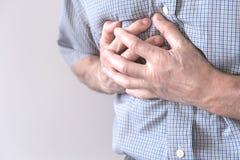 De jonge man lijdt aan borstpijn Borstkramp, angina pectoris De mens houdt voor hart stock afbeeldingen