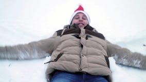 De jonge man maakt een engel in de sneeuw stock footage