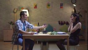 De jonge man maakt tot een aanbieding aan een mooie vrouw op een romantische datum stock video