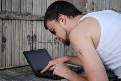 De jonge man met de computer Stock Foto's