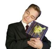 De jonge man met een glimlach een het omhelzen gift Royalty-vrije Stock Foto's