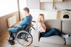 De jonge man met speciale behoeften en de gezonde vrouw zitten rijtjes in ruimte Debatteer en quirrel Arbeider met handicap en stock afbeelding