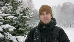 De jonge man onderzoekt de camera en het glimlachen in de winter bos Grote sneeuwval Een mens in een donker jasje en een warme ho stock videobeelden