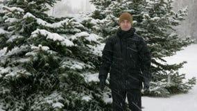 De jonge man onderzoekt de camera en het glimlachen in de winter bos Grote sneeuwval Het spelen met sneeuw Een mens in dark stock footage