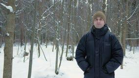 De jonge man onderzoekt de camera en het glimlachen in de winter bos Sneeuwlandschap Een mens in een donker jasje en een warme ho stock footage
