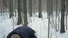 De jonge man onderzoekt de camera en het glimlachen in de winter het bos Spelen met sneeuw Een mens in een donker jasje en warm stock video